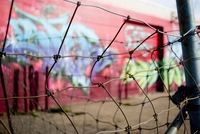 Graffiti behind wire fence