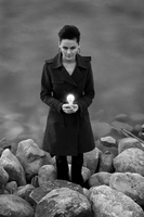 Girl holding light bulb standing on rocks
